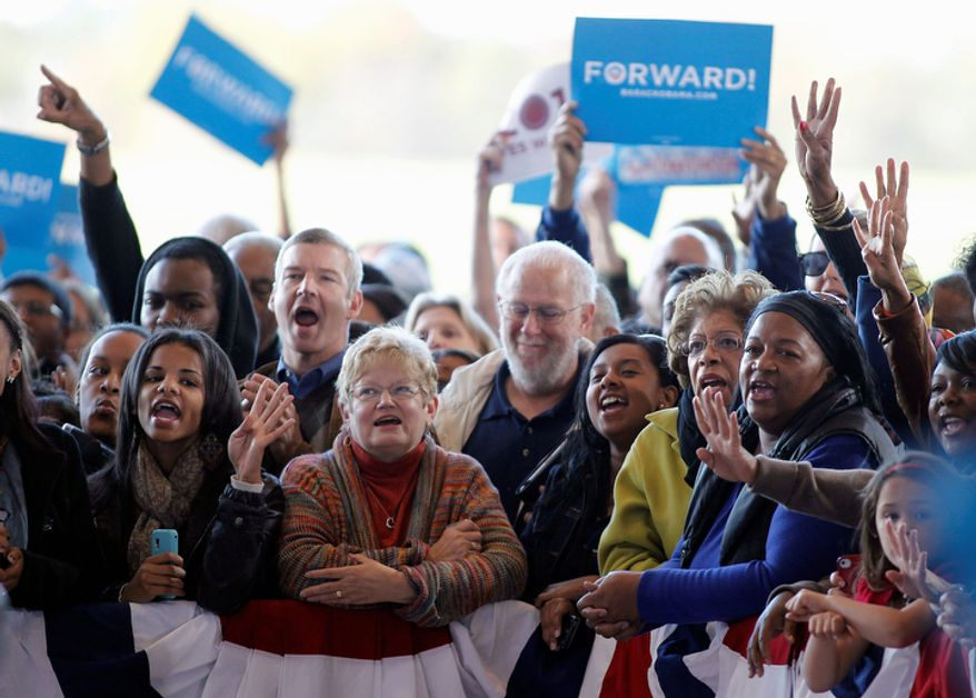Supporters cheer as first lady Michelle Obama speaks at a campaign rally in a hangar at the Charlotte Douglas International Airport in Charlotte, N.C., Monday, Nov. 5, 2012. (AP Photo/Bob Leverone)