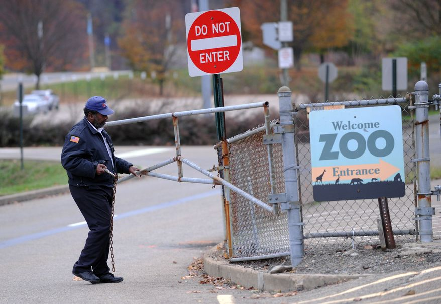 A security guard closes the gate at the Pittsburgh Zoo, where officials say a young boy was killed after he fell into the exhibit that was home to a pack of African painted dogs, which pounced on the child and mauled him on Sunday, Nov. 4, 2012. (AP Photo/John Heller)