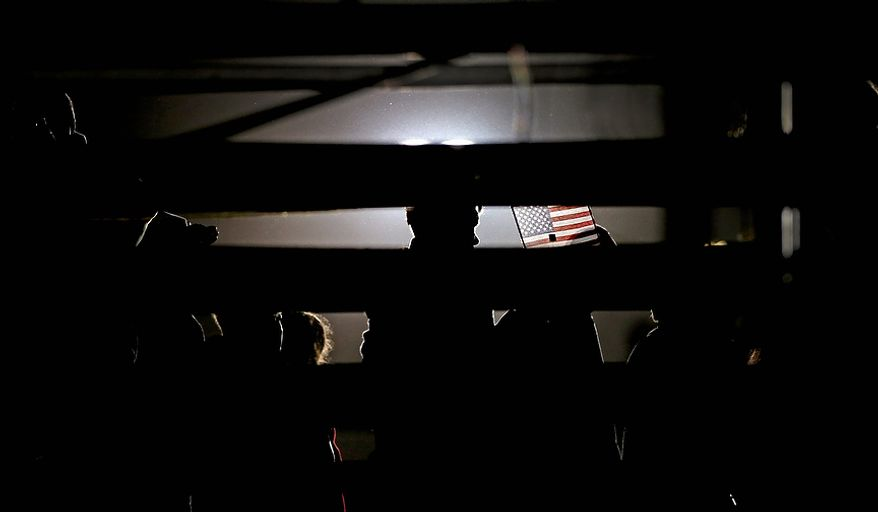 A member of the crowd holds a United States flag behind bleachers after Republican presidential candidate Mitt Romney delivered a speech at a campaign event at Shady Brook Farm on Sunday, Nov. 4, 2012, in Morrisville, Pa. (AP Photo/David Goldman)