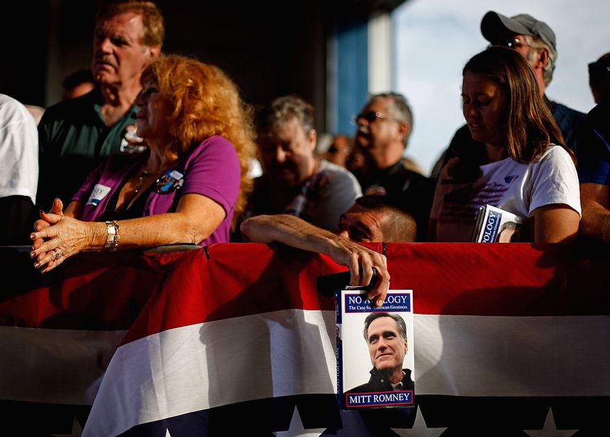 Shawn Moore of Orlando, Fla., holds on to his copy of the book by Republican presidential candidate Mitt Romney as he bends down to pick up a sign he dropped while waiting for Mr. Romney to appear at a campaign event at the Orlando Sanford International Airport on Monday, Nov. 5, 2012, in Sanford, Fla. (AP Photo/David Goldman)