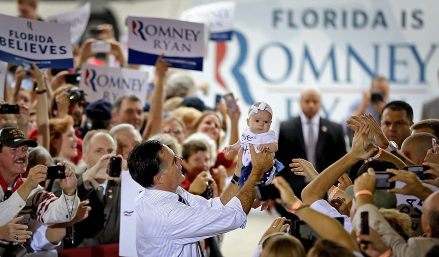 Republican presidential candidate Mitt Romney picks up a baby as he walks through the crowd before stepping onstage at a campaign event at Orlando Sanford International Airport on Monday, Nov. 5, 2012, in Sanford, Fla. (AP Photo/David Goldman)