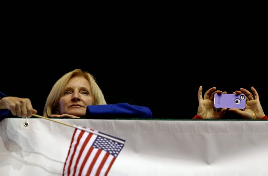 A crowd member takes a photo with a mobile phone at right as another watches Republican presidential candidate, former Massachusetts Gov. Mitt Romney speak during a campaign event at The Patriot Center at George Mason University, Monday, Nov. 5, 2012, in Fairfax, Va. (AP Photo/David Goldman)