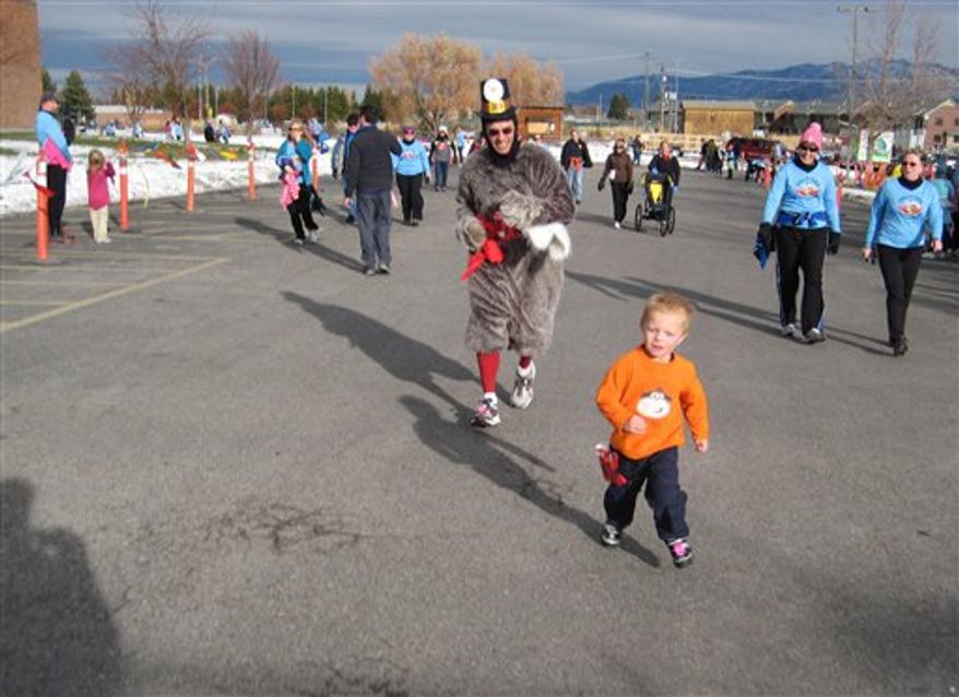 This Nov. 24, 2011 photo courtesy of Kalli Ryti shows her son, Cooper Bourret, racing a turkey to the finish line at the Huffing for Stuffing Thanksgiving Day Run in Bozeman, Mont. Ryti runs the race with her family every year before enjoying a turkey dinner. (AP Photo/Courtesy Kalli Ryti, Mike Bourret)