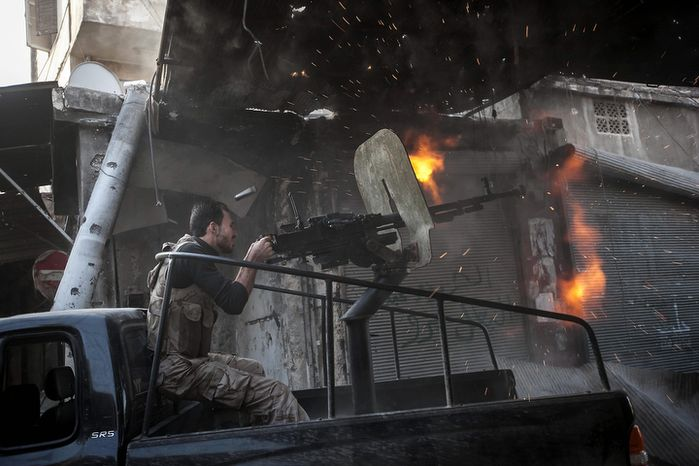 A rebel fighter fires a gun Nov. 4, 2012, toward a building where Syrian troops loyal to President Bashar Assad are hiding while they attempt to gain terrain against the rebels during heavy clashes in the Jedida district of Aleppo, Syria. (Associated Press)