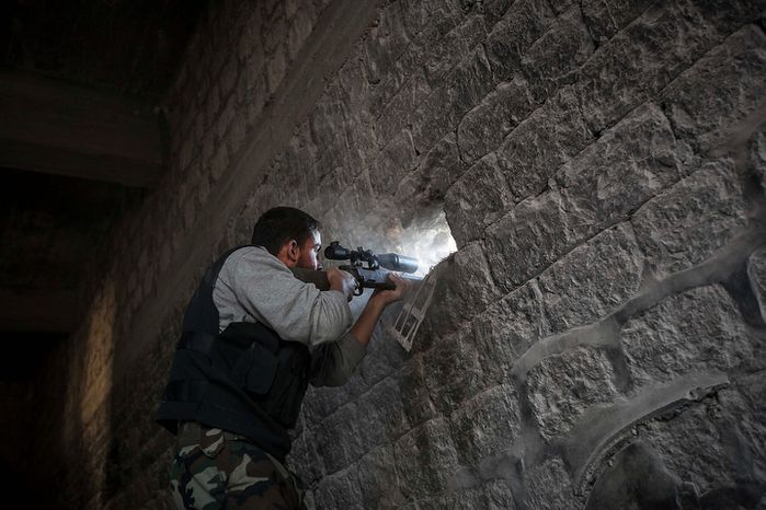 A rebel sniper aims Nov. 4, 2012, through a hole in the wall that overlooks a position held by Syrian troops loyal to President Bashar Assad hidden in a nearby building as they attempt to gain ground on the rebel lines during heavy clashes in the Jedida district of Aleppo, Syria. (Associated Press)