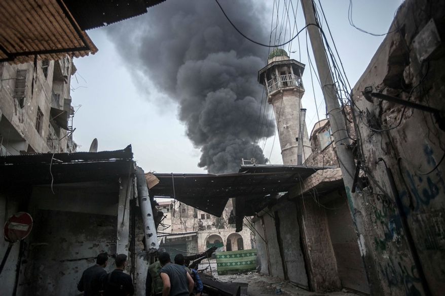 Rebel fighters watch Nov. 4, 2012, as smoke rises after Syrian government forces fired an artillery round at a rebel position during heavy clashes in the Jedida district of Aleppo, Syria. (Associated Press)