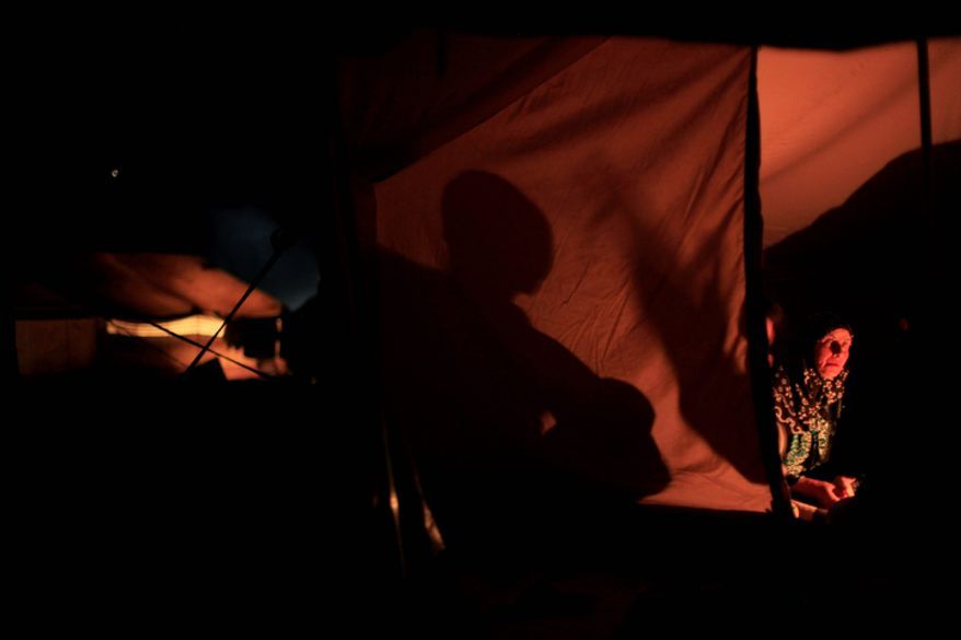 A Syrian woman who fled the violence in her village sits Nov. 4, 2012, in tent at a camp in the Syrian village of Atma, near the Turkish border with Syria. (Associated Press)