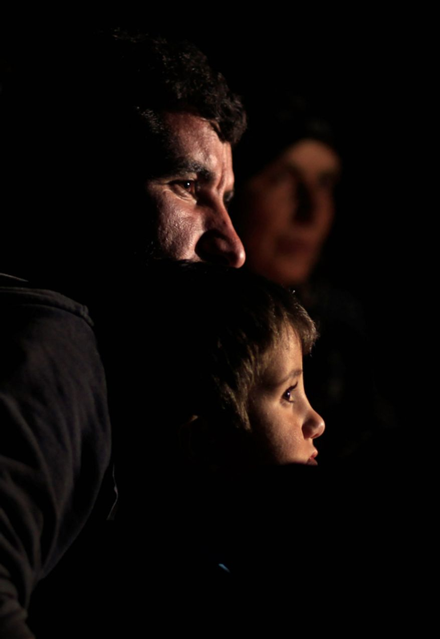 A Syrian family who fled violence in their village sit Nov. 4, 2012, in front of a fire next to their tent at a camp for the internally displaced in the Syrian village of Atma, near the Turkish border with Syria. (Associated Press)