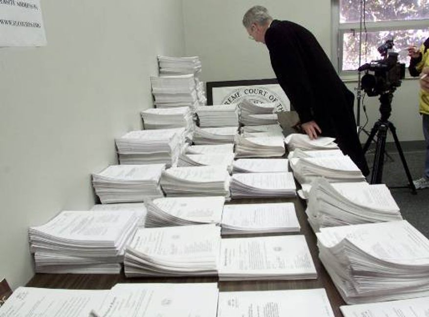 Thomas D. Hall, clerk of the Florida Supreme Court, looks over a stack of pleadings filed with the court since Nov. 15, 2000, in Tallahassee, Fla., as the justices continue on Tuesday, Nov. 21, 2000, to deliberate on the certification of the Florida presidential vote by the secretary of state. (AP Photo/Beth A. Keiser, Pool)