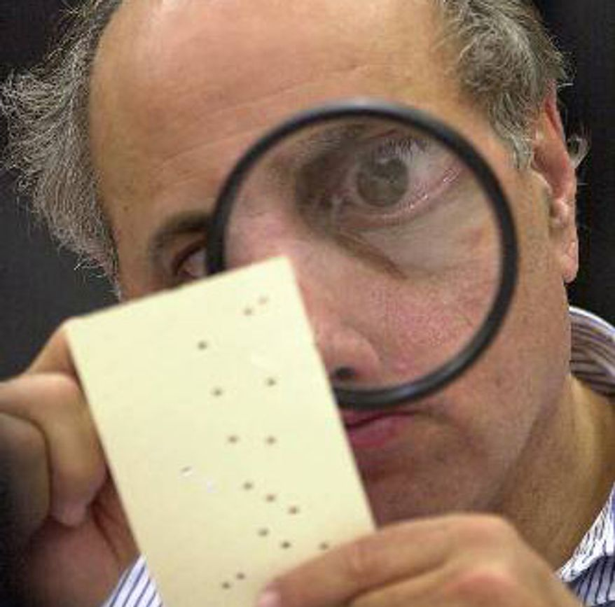 An election judge uses a magnifying glass to inspect a ballot during a recount after the 2000 presidential election.