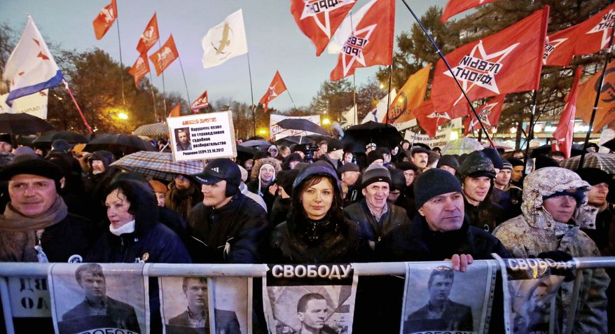 Demonstrators hold posters with portraits of jailed opposition activists Vladimir Akimenkov and Leonid Razvozzhayev during a rally in Moscow on Oct. 30. The rally went on peacefully amid heavy police cordons. Russian President Vladimir Putin has insisted that no one is in prison for opposing his policies. (Associated Press)