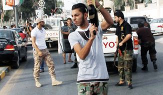 A Libyan militiaman fires in the air in an attempt to force back protesters from in front of the gates of the parliament in Tripoli, Libya, in October. One year on, the country is still trying to overcome the legacy of one of the most erratic leaders of modern times as well as a brutal eight-month struggle that left the country awash in weapons, militias and very few state institutions. (Associated Press)