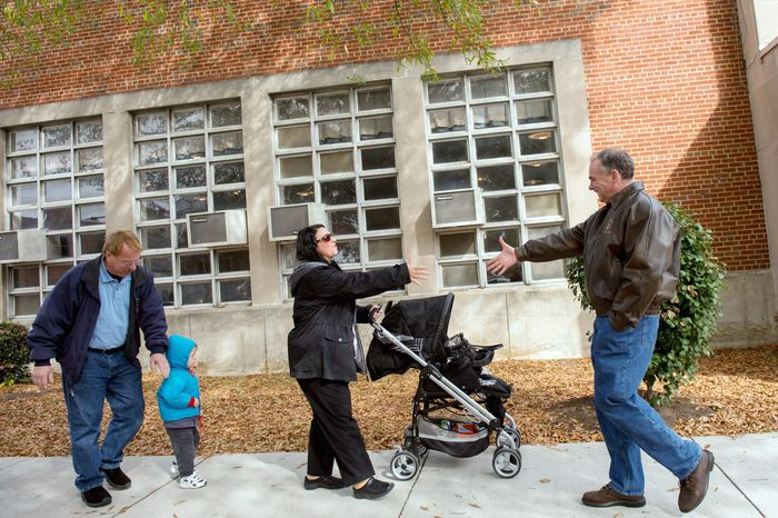 Michael and Laura Macario and their grandson Maxwell, 2, are greeted by Democratic candidate for Senate Tim Kaine, right, as they arrive to vote outside the polling entrance to G.W. Carver Elementary School on election day morning, Richmond, Va., Tuesday, November 6, 2012. (Andrew Harnik/The Washington Times)