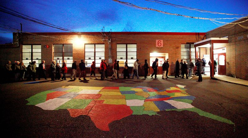 A steady stream of voters make their way to the voting site at Washington Mill Elementary School in Fairfax County past a map of the U.S. just after 6 a.m. on Election Day to vote for their chosen candidates. (Eva Russo/Special to The Washington Times) ** FILE **