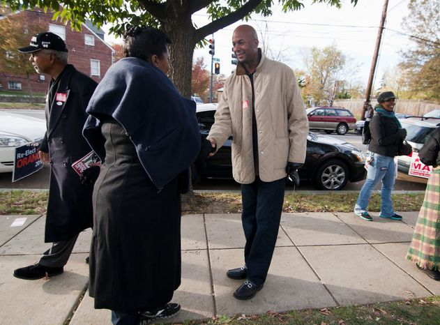 Incumbent at-large D.C. Council member Michael A. Brown (left), a Democrat, makes a last campaign pitch to voters outside a Precinct 110 polling site Tuesday. There were five challengers for his and another at-large seat. (Craig Bisacre/The Washington Times)