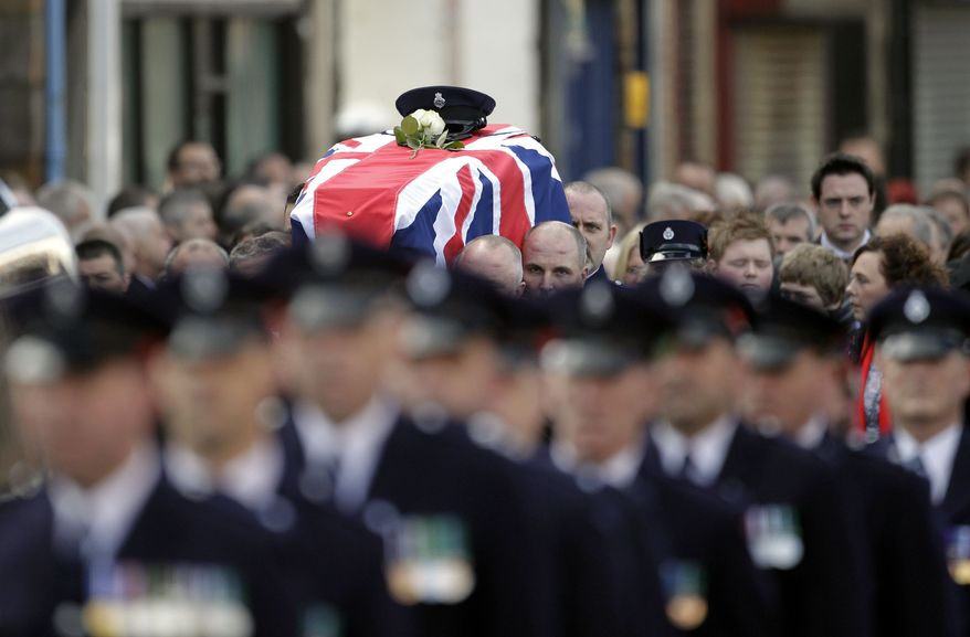 Prison officers carry the coffin of their slain colleague, David Black, to Molesworth Presbyterian Church in Cookstown, Northern Ireland, on Tuesday, Nov. 6, 2012. The father of two was shot dead by suspected paramilitary Irish Republican Army dissidents in County Armagh on Thursday as he drove to work at Maghaberry Prison. (AP Photo/Peter Morrison)
