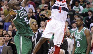 Washington Wizards forward Martell Webster (9) takes a shot against Boston Celtics forward Kevin Garnett (5) during the second half of an NBA basketball game, Saturday, Nov. 3, 2012, in Washington. The Celtics won 89-86. (AP Photo/Nick Wass)