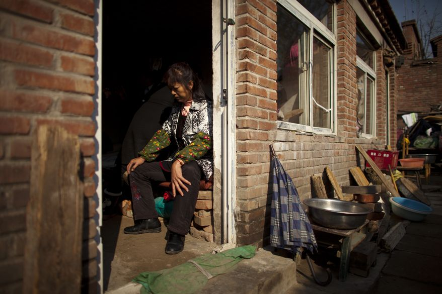 A recently arrived petitioner from southern China's Hunan province rests on the bed of a rental room that was raided by unidentified men a week ago, on the outskirts of Beijing on Tuesday, Nov. 6, 2012. (AP Photo/Alexander F. Yuan)