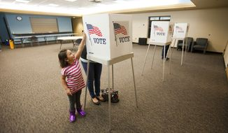 Baylee Hernandez, 4, plays next to her mother Britni Tortora, of Arvada, Colo., while she votes Nov. 6, 2012, at the Apex Center in Arvada. (Associated Press)