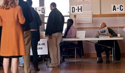 A volunteer check-in clerk reads the newspaper while waiting for constituents to cast their votes during the lunch time hours at Wesley Methodist Church, precinct 32, Washington, D.C., Tuesday, Nov. 6, 2012 (Craig Bisacre/The Washington Times)