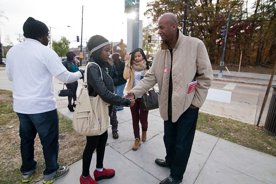 At large D.C. Council Member, Michael Brown, greets voters outside of precinct 103 polling site in Washington, D.C., to cast their vote, Tuesday, Nov. 6, 2012 (Craig Bisacre/The Washington Times)
