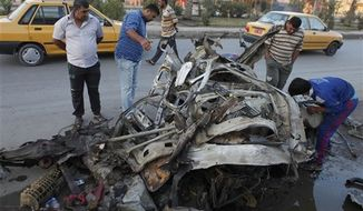 ** FILE ** Iraqis inspect the aftermath of Saturday's car bomb explosion, in the Shiite enclave of Sadr City, in Baghdad, Iraq, Sunday, Oct. 28, 2012. Iraqi insurgents unleashed a string of bombings and other attacks that killed and wounded scores of people, primarily targeting the country's Shiite community on Saturday, Oct. 27, 2012, in a challenge to government efforts to promote a sense of stability by preventing attacks during a major Muslim holiday. (AP Photo/Karim Kadim)