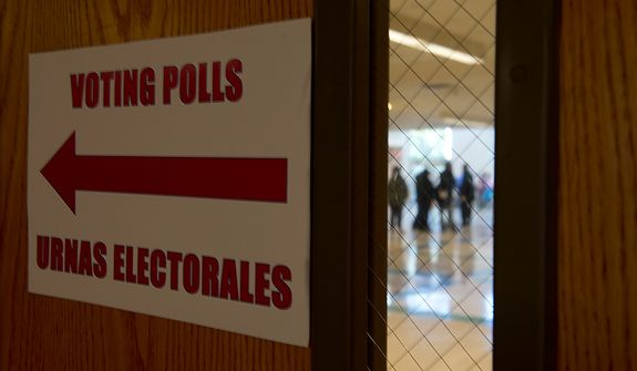 Voters waiting to cast ballots on Election Day at Winston Churchill High School in Potomac, Md., are seen through a cafeteria door on Nov. 6, 2012. (Barbara L. Salisbury/The Washington Times)