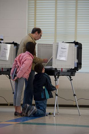Macafie (left), 10, and Anthony Bobo, 8, look on as their father, Jack, votes on Election Day at Winston Churchill High School in Potomac, Md., on Nov. 6, 2012. (Barbara L. Salisbury/The Washington Times)