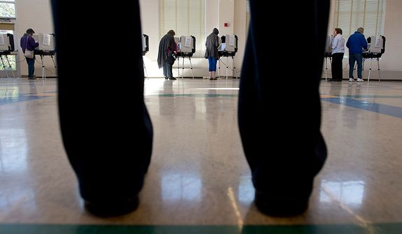 While one man waits for an election official to bring him to an available voting machine, other voters cast their ballots at Winston Churchill High School in Potomac, Md. on Election Day, Nov. 6, 2012. (Barbara L. Salisbury/The Washington Times)