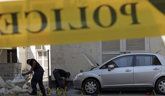 Bahraini policemen search for evidence Nov. 5, 2012, at the scene of an explosion that killed an Asian man in Manama, Bahrain. (Associated Press)
