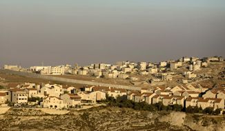 **FILE** The Jewish neighborhood of Pisgat Zeev in east Jerusalem is seen here on July 29, 2009, with the Shuafat refugee camp (background) and Israel's separation barrier running between them. (Associated Press)