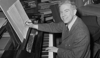 Pulitzer Prize-winning composer Elliott Carter poses at the piano in his New York apartment in 1960 after the announcement of the award was made. (AP Photo/John Lent)