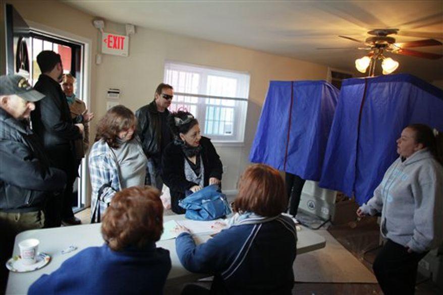 People cast their votes, Tuesday, Nov. 6, 2012, at a 1st Ward polling location in South Philadelphia. (AP Photo/ Joseph Kaczmarek)