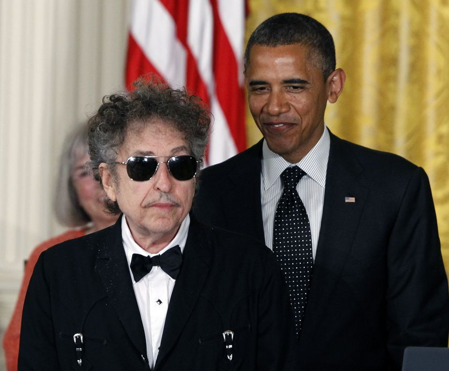 **FILE** President Obama stands with Bob Dylan before awarding him the Medal of Freedom during a May 29, 2012, ceremony in the East Room of the White House. (Associated Press)