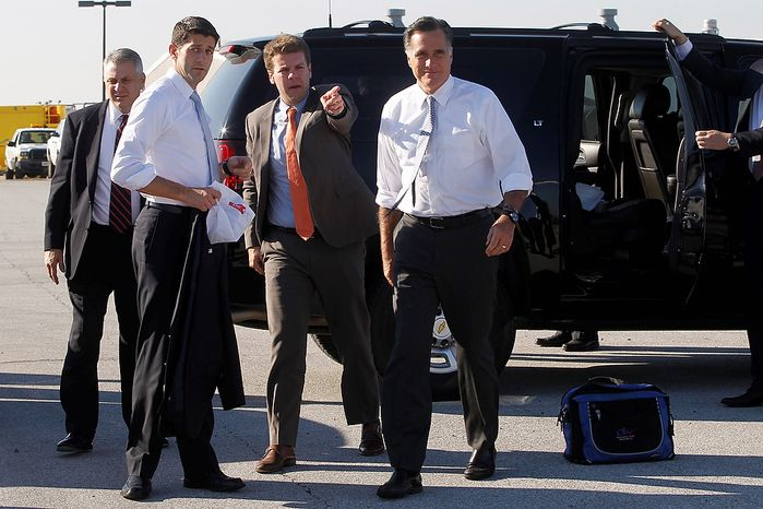 A staff member gives Republican presidential candidate, former Massachusetts Gov. Mitt Romney, right and his running mate Rep. Paul Ryan, R-Wis., directions on where to proceed after they arrived at Cleveland Hopkins International Airport, Tuesday, Nov. 6, 2012 in Cleveland, Ohio, before boarding their respective campaign planes.  (AP Photo/Mary Altaffer)