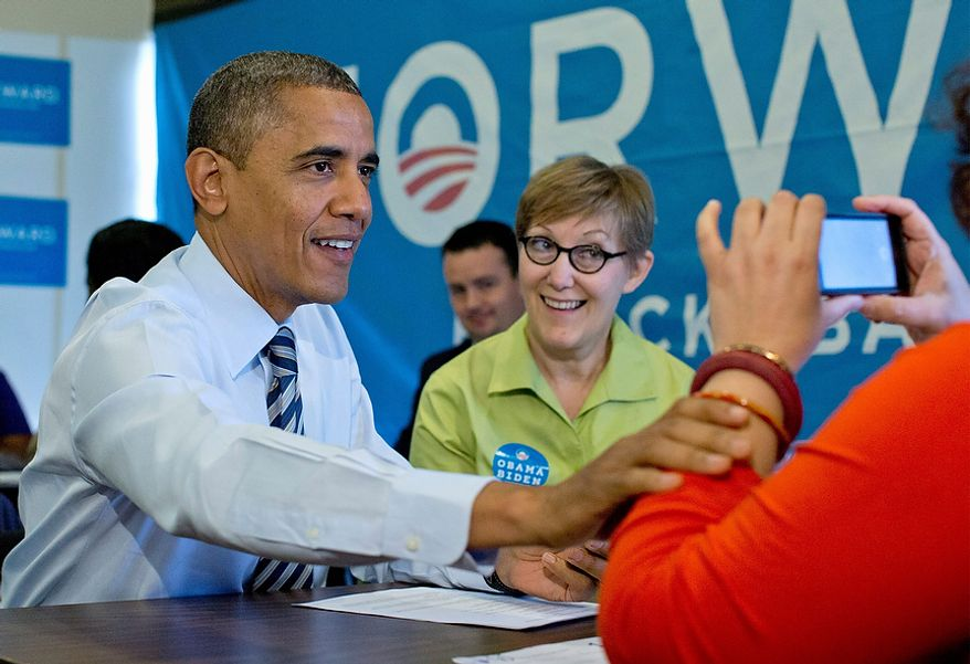 President Barack Obama has his photo taken during a visit with volunteers, including Carla Windhorst, second from left, at campaign office call center the morning of the 2012 election, Tuesday, Nov. 6, 2012, in Chicago. (AP Photo/Carolyn Kaster)