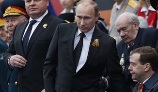 ** FILE ** Russian Defense Minister Anatoly Serdyukov (left), President Vladimir Putin (center) and Prime Minister Dmitry Medvedev (bottom right) watch the Victory Day parade in Moscow on Wednesday, May 9, 2012. (AP Photo/Alexander Zemlianichenko)