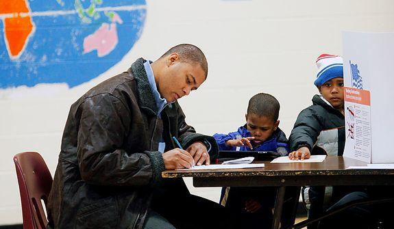 Jovan Velasquez votes as his children Julian (center), 3, Jaylen, 5, and Jovan Jr. (not shown), 8, watch Nov. 6, 2012, at Washington Mill Elementary School in Alexandria, Va. (Eva Russo/Special to The Washington Times)