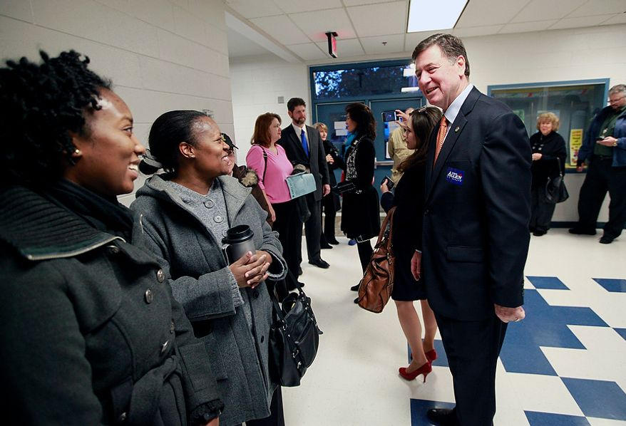 George Allen, U.S. Senate candidate in Virginia, greets first-time voter Nysha Harris (left) and her mother, Tamica Harris, as they wait in line to vote at Washington Mill Elementary School in Alexandria, Va., on Nov. 6, 2012. Allen was also there to vote with his wife, Susan. (Eva Russo/Special to The Washington Times)