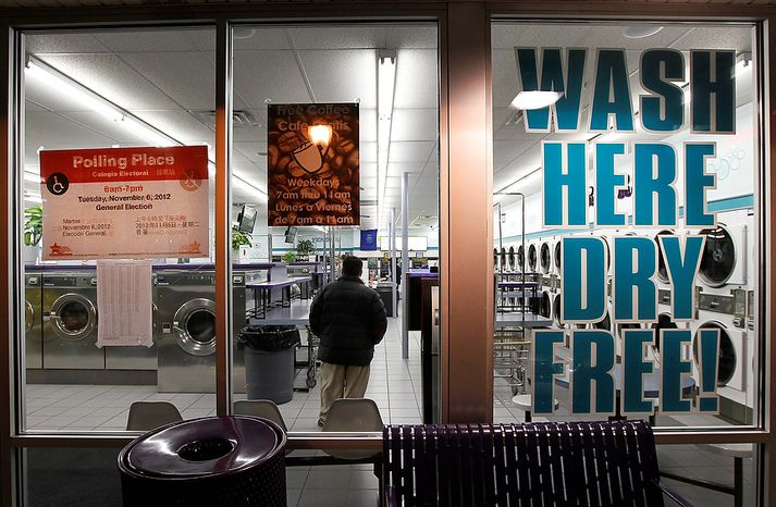 Matt Kamien waits to vote inside the 24-hour Su Nueva Laundromat in Chicago's 13th Ward on Election Day, Tuesday, Nov. 6, 2012. (AP Photo/Charles Rex Arbogast)