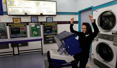 Leslie Fabian reacts after successfully voting electronically on Election Day at the 24-hour Su Nueva Laundromat in Chicago's 13th Ward on Tuesday, Nov. 6, 2012. (AP Photo/Charles Rex Arbogast)