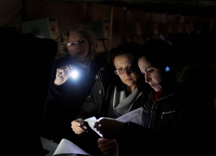 Poll workers (from right) Eva Prenga, Roxanne Blancero and Carole Sevchuk try to start an optical scanner voting machine in the cold and dark at a polling station in a tent in the Midland Beach section of Staten Island in New York on Tuesday, Nov. 6, 2012. The original polling site, a school, was damaged by superstorm Sandy. (AP Photo/Seth Wenig)