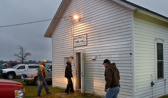 Early morning voters were not deterred by the cold rain Tuesday, Nov. 6, 2012, as they come to cast their ballots at Haverhill Town Hall, northeast of Rochester, Minn.  Americans are heading to polling places across the country Tuesday.  (AP Photo/The Rochester Post-Bulletin, Jerry Olson)