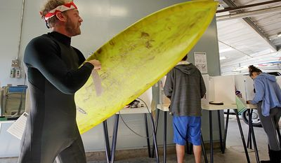 """After voting, Mike Weigart, 30, carries his ballot and his surfboard to the ballot box at the polling place at the Venice Beach lifeguard headquarters in Los Angeles Tuesday, Nov. 6, 2012. Weigart said """"It's awesome the polling place is where I surf."""" (AP Photo/Reed Saxon)"""