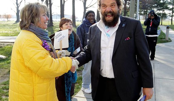 "Indiana gubernatorial candidate Libertarian Rupert Boneham laughs as he's told by poling place volunteer Carol Mapier that he ""has a great body"" as he greeted voters outside a poling place in Indianapolis, Tuesday, Nov. 6, 2012.  Boneham faces Democrat John Gregg and Republican Mike Pence in the gubernatorial race. Boneham was a contestant on the reality show Survivor. (AP Photo/Michael Conroy)"