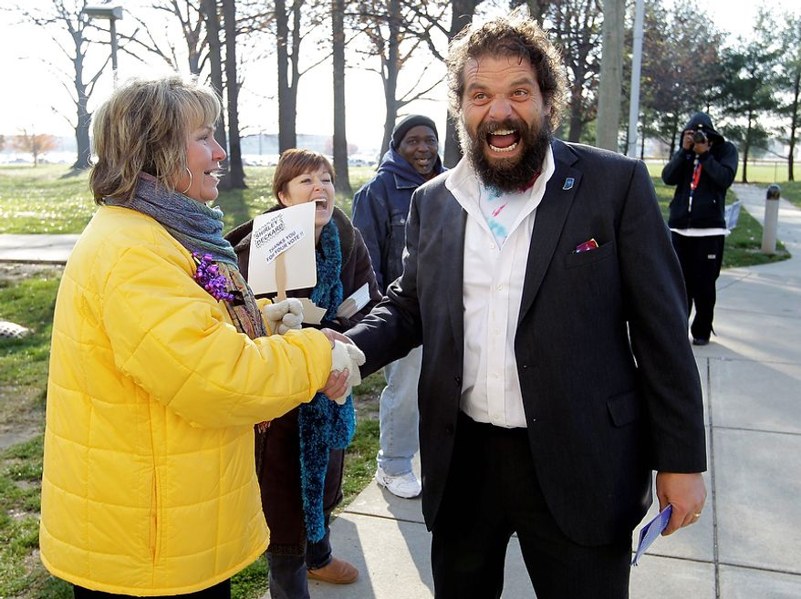 """Indiana gubernatorial candidate Libertarian Rupert Boneham laughs as he's told by poling place volunteer Carol Mapier that he """"has a great body"""" as he greeted voters outside a poling place in Indianapolis, Tuesday, Nov. 6, 2012.  Boneham faces Democrat John Gregg and Republican Mike Pence in the gubernatorial race. Boneham was a contestant on the reality show Survivor. (AP Photo/Michael Conroy)"""
