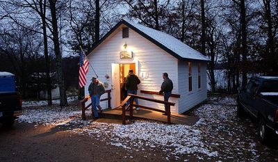 A light wet snow covers the roof and ground around the Jenkins Town Hall as early voters casts their ballots Tuesday, Nov. 6, 2012 in Jenkins, Minn. Jenkins is located in Crow Wing County in northern Minnesota. (AP Photo/Tom Olmscheid)