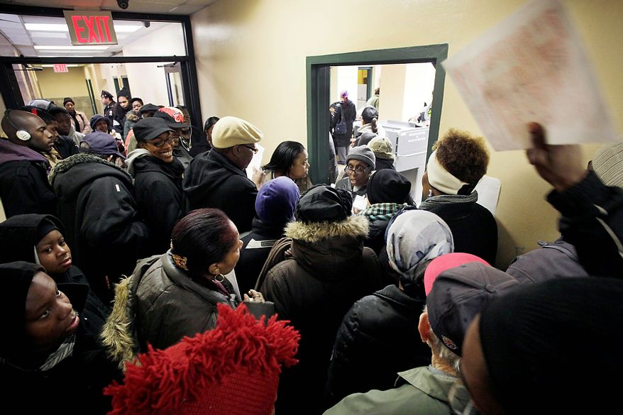 A man tries to hand his ballot, top right, to an election worker, standing in the doorway, as voters crowd an apartment building hallway, Tuesday, Nov. 6, 2012 in the Coney Island section of New York. Voting in the U.S. presidential election was the latest challenge for the hundreds of thousands of people in the New York-New Jersey area still affected by Superstorm Sandy, as they struggled to get to non-damaged polling places to cast their ballots in one of the tightest elections in recent history. AP Photo/Mark Lennihan)