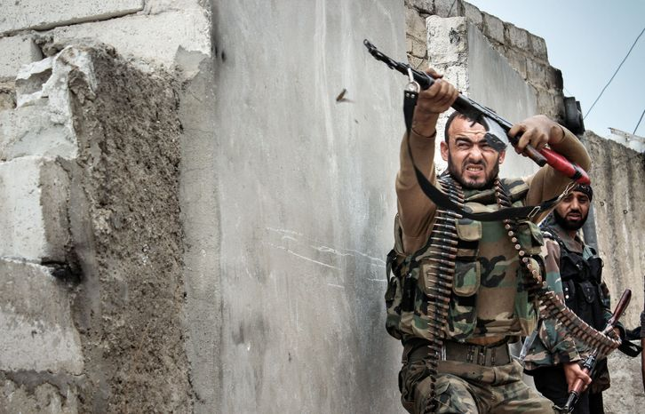 ** FILE ** In this Nov. 7, 2012, file photo, a Syrian rebel fires at snipers in Harem, Syria. (Associated Press)
