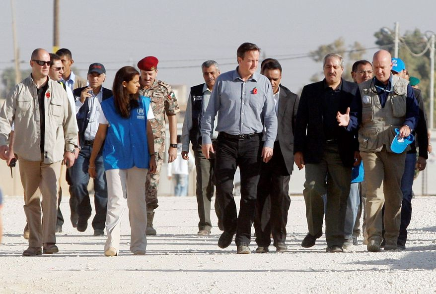 """Britain's Prime Minister David Cameron, center, walks with Jordanian Foreign Minister Nasser Judeh, second left, and United Nations High Commissioner for Refugees (UNHCR) representative to Jordan Andrew Harper, right, during his visit to Zaatari refugee camp in Mafraq, Jordan, Wednesday, Nov. 7, 2012. British Prime Minister David Cameron, visiting a camp for Syrian refugees in Jordan, said the U.S., Britain and other allies should do more to """"shape the opposition"""" into a coherent force and open channels of communication directly with rebel military commanders. Previously, Britain and the U.S. have acknowledged contacts only with exile groups and political opposition figures inside Syria. (AP Photo)"""